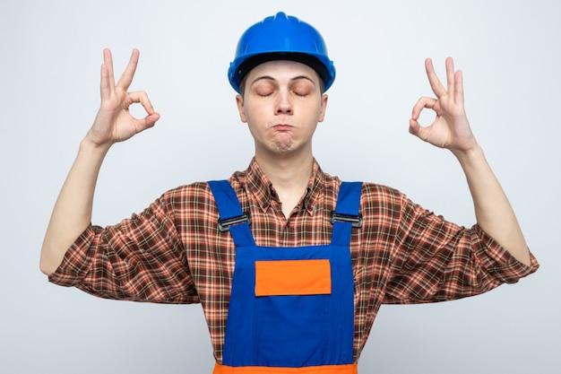 Met gesloten ogen meditatie doen jonge mannelijke bouwer uniform dragen