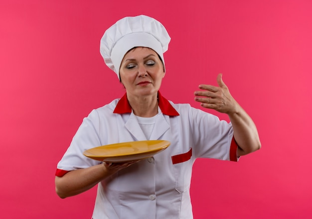 Met gesloten ogen middelbare leeftijd vrouwelijke kok in chef-kok uniform prtend snuiven bedrijf plaat