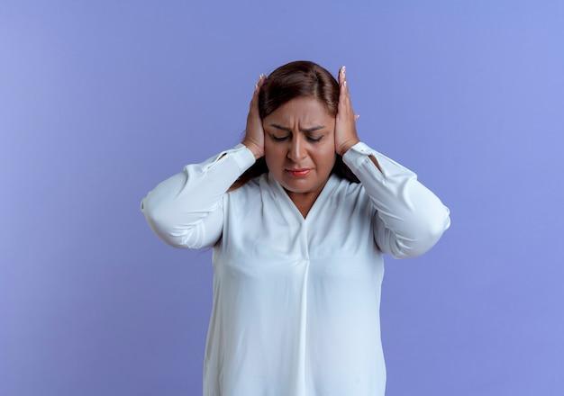 Met gesloten ogen moe casual blanke vrouw van middelbare leeftijd greep hoofd geïsoleerd op blauwe muur