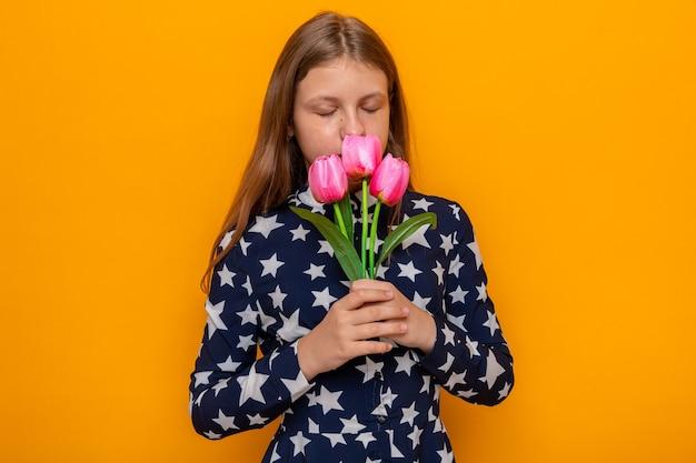 Met gesloten ogen mooi klein meisje dat bloemen vasthoudt en snuift geïsoleerd op een oranje muur