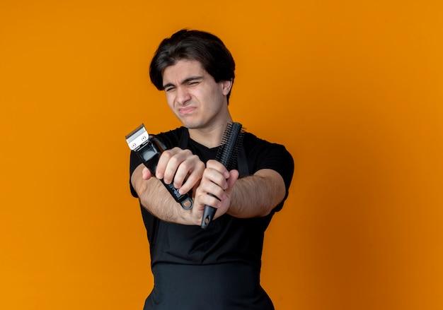 Met gesloten ogen onaangename jonge knappe mannelijke kapper in uniform bedrijf en kruising van haartrimmers met kam geïsoleerd op een oranje achtergrond