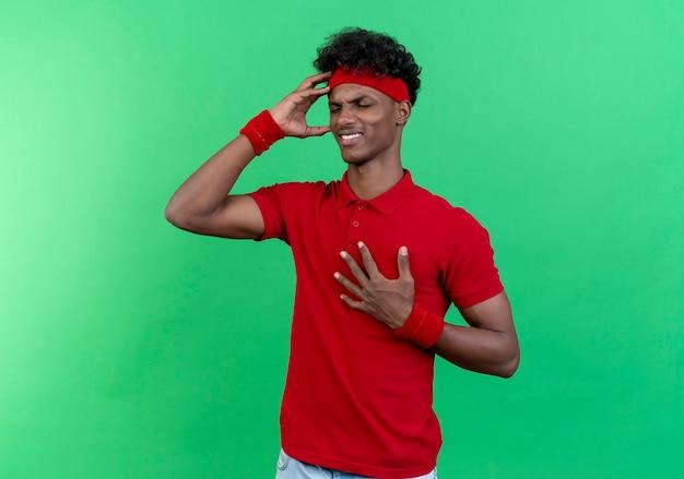 Met gesloten ogen onaangename jonge sportieve man met hoofdband