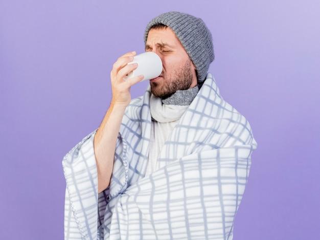 Met gesloten ogen onaangename jonge zieke man met winter hoed met sjaal het drinken van thee geïsoleerd op paarse achtergrond
