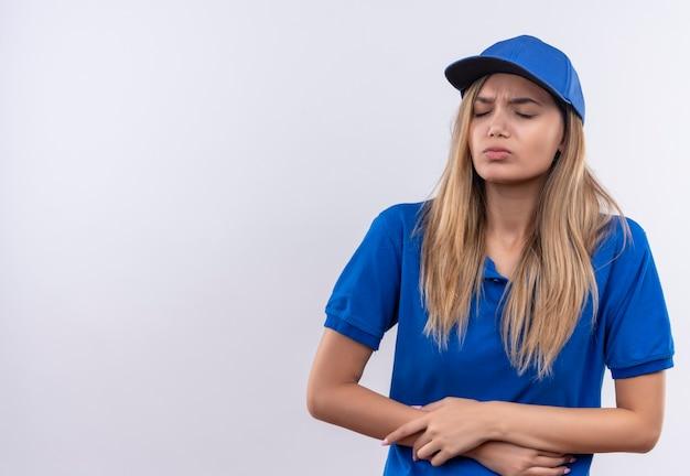Met gesloten ogen pakte het jonge bezorgmeisje dat een blauw uniform en een pet droeg pijnlijke maag op wit wordt geïsoleerd