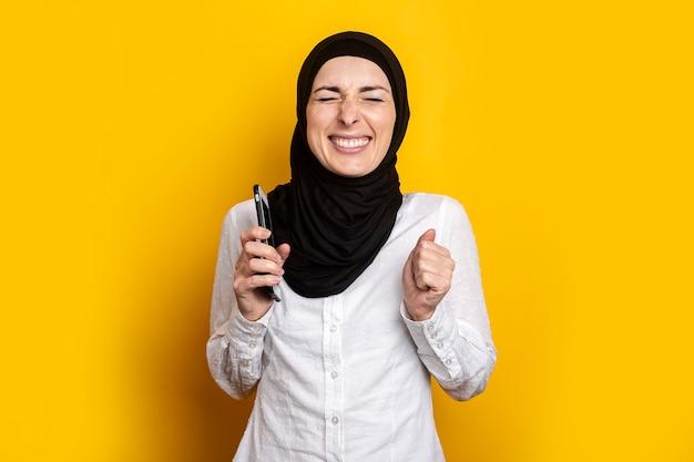 Met gesloten ogen sloot een jonge vrouw in een hijab haar ogen met een gele telefoon.