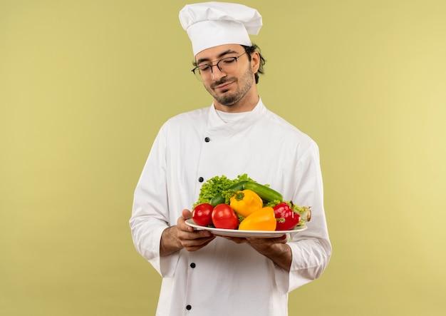 Met gesloten ogen tevreden jonge mannelijke kok die eenvormige chef-kok en glazen draagt die groenten op plaat houden die op groene muur wordt geïsoleerd