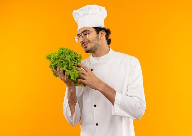Met gesloten ogen tevreden jonge mannelijke kok die eenvormige chef-kok en glazen draagt die salade houden die op gele muur wordt geïsoleerd