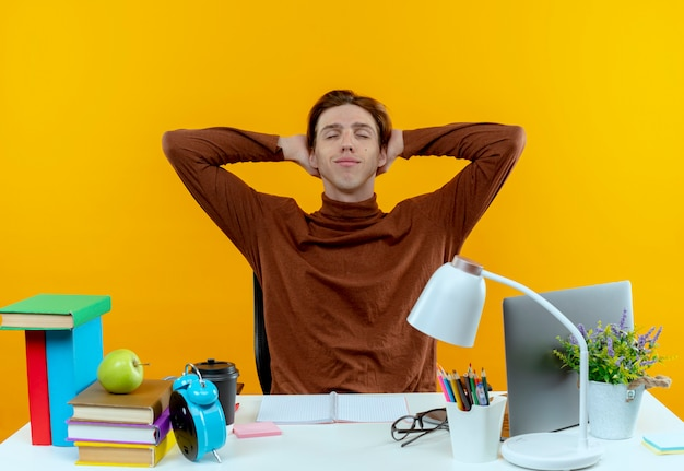 Met gesloten ogen tevreden jonge studentenjongen zittend aan een bureau met schoolhulpmiddelen hand achter het hoofd op geel te houden