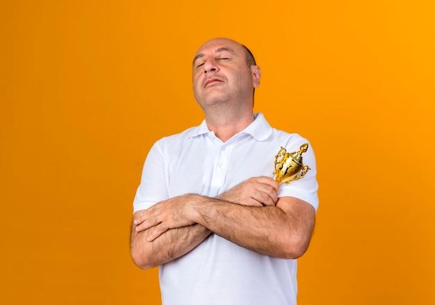 Met gesloten ogen toevallige volwassen man die handen kruist en winnaarbeker houdt die op gele muur wordt geïsoleerd