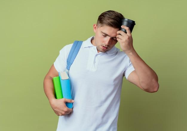 Met gesloten ogen vermoeide jonge knappe mannelijke student die achterzak draagt die boeken houdt en kop van koffie op voorhoofd zet die op olijfgroen wordt geïsoleerd