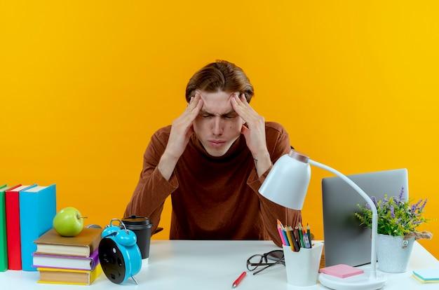 Met gesloten ogen vermoeide jonge studentenjongen zittend aan een bureau met schoolhulpmiddelen die hand rond de ogen zetten die op gele muur worden geïsoleerd