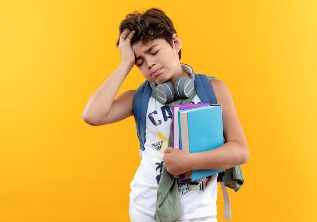 Met gesloten ogen vermoeide kleine schooljongen die rugtas en koptelefoon draagt die boeken houdt en het hoofd grijpt dat op geel wordt geïsoleerd