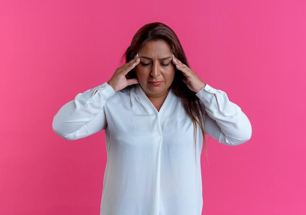 Met gesloten ogen vermoeide toevallige kaukasische vrouw van middelbare leeftijd die handen op voorhoofd zetten dat op roze muur wordt geïsoleerd