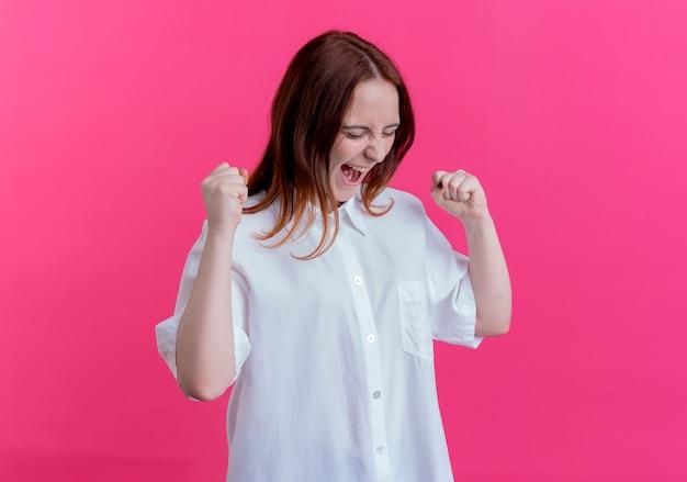 Met gesloten ogen vrolijk jong roodharigemeisje die ja gebaar tonen dat op roze achtergrond wordt geïsoleerd