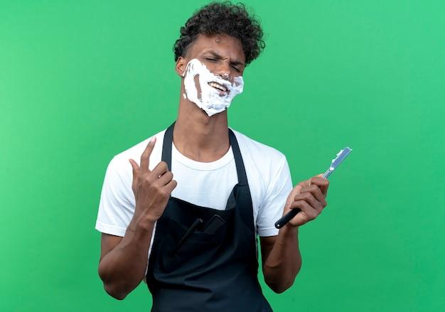 Met gesloten ogen vrolijke jonge afro-amerikaanse mannelijke kapper in uniform met scheerschuim aangebracht op zijn gezicht met open scheermes