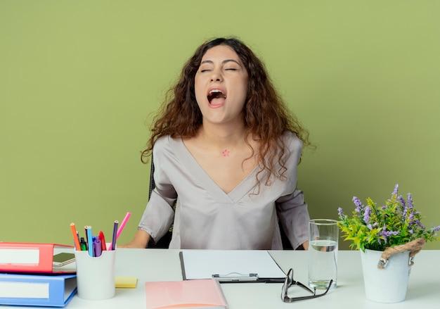 Met gesloten ogen vrolijke jonge mooie vrouwelijke kantoormedewerker zittend aan een bureau met kantoorhulpmiddelen geïsoleerd op olijf achtergrond