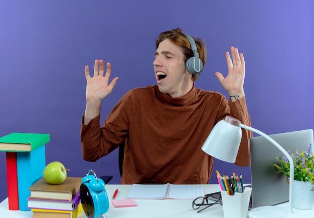 Met gesloten ogen vrolijke jonge student zittend aan een bureau met schoolhulpmiddelen luisteren muziek op koptelefoon en spreidt handen op paars