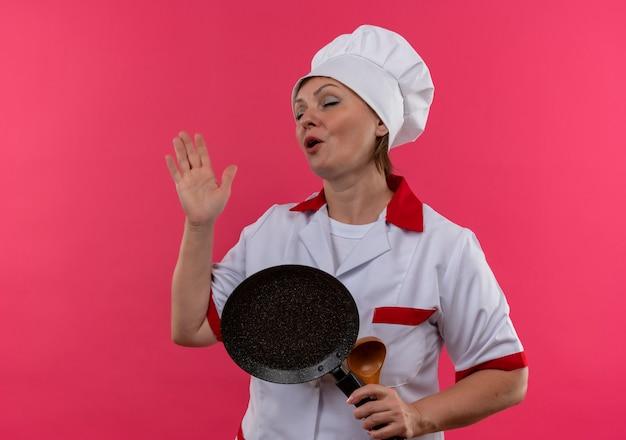 Met gesloten ogen vrouwelijke kok van middelbare leeftijd in de pan van de chef-kok de eenvormige holding en zingt