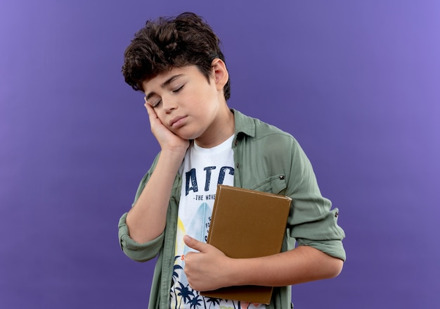 Met gesloten ogen zieke kleine schooljongen met boek en hand op wang geïsoleerd op paarse muur