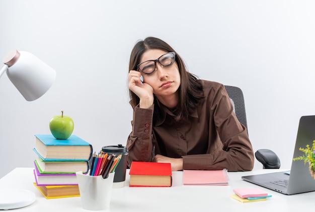 Met gesloten ogen zit de vermoeide jonge schoolvrouw met een bril aan tafel met schoolgereedschap hand op de wang