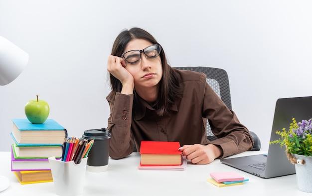 Met gesloten ogen zit een jonge schoolvrouw met een bril aan tafel met schoolgereedschap