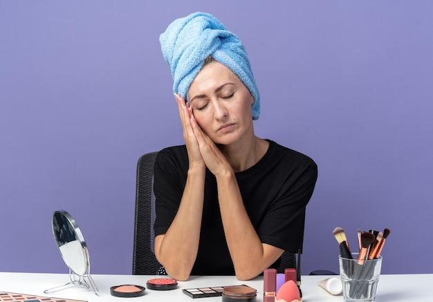 Met gesloten ogen zit jong mooi meisje aan tafel met make-up tools haar in handdoek afvegen met slaap gebaar geïsoleerd op blauwe achtergrond