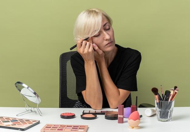 Met gesloten ogen zit jong mooi meisje aan tafel met make-up tools teken pijl met eyeliner geïsoleerd op olijfgroene achtergrond