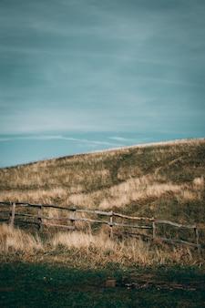 Met gras begroeide heuvels met houten hek