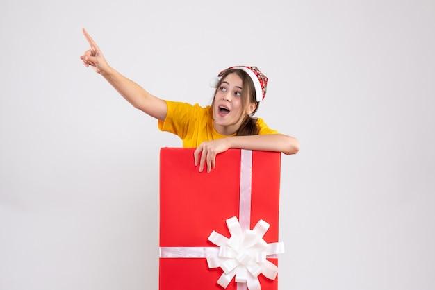 Met grote ogen meisje met kerstmuts wijzend op iets achter grote xmas gift op wit