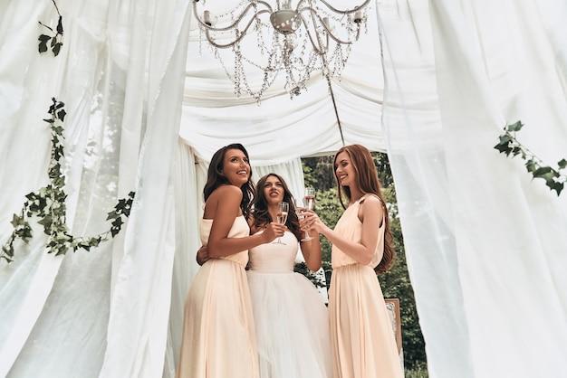 Met haar dames aan haar zijde. aantrekkelijke jonge bruid die champagne drinkt met haar mooie bruidsmeisjes terwijl ze buiten staat