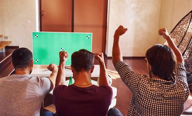 Met handen omhoog. opgewonden drie vrienden die samen thuis voetbal kijken op tv.