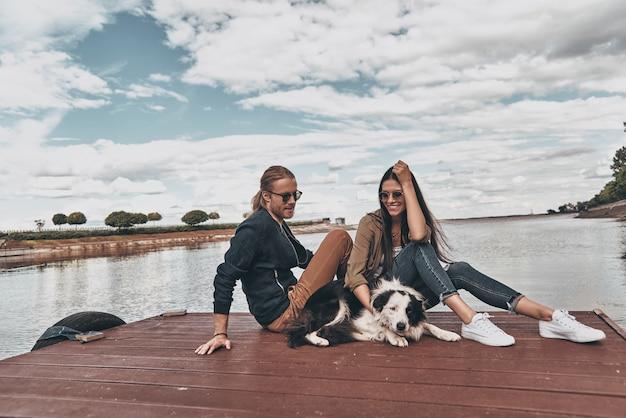 Met hun beste vriend. mooie jonge paar glimlachend zittend op het houten platform bij de rivier