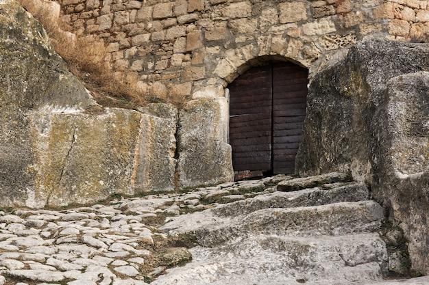 Met ijzer omzoomde poort naar een middeleeuwse grotstad-fort chufut-kale, crimea