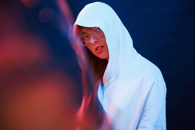 Met interesse naar je kijken. studio opname in donkere studio met neonlicht. portret van een jong meisje