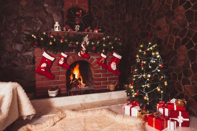 Met kerst versierde open haard en boom in de kamer