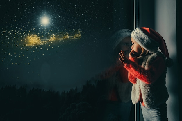 Met kerstmis kijkt het kind uit het raam Premium Foto