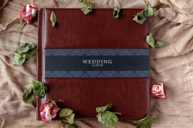 Met leer bedekt bruiloft fotoalbum bovenaanzicht met roze bloemen decoratie