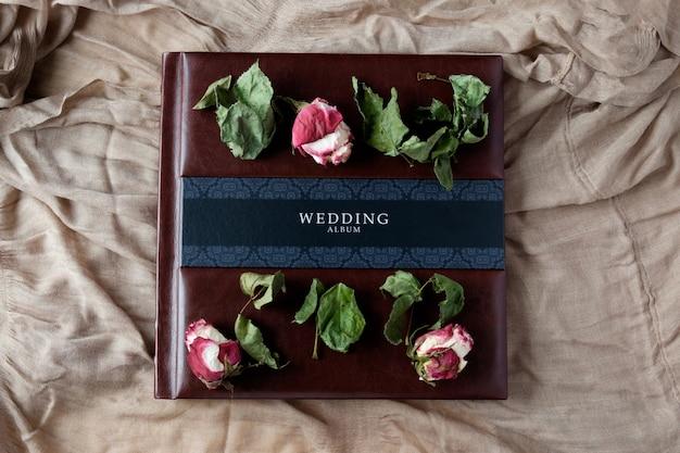 Met leer beklede bruiloft fotoalbum bovenaanzicht met roze bloemen decoratie
