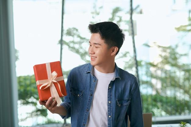 Met liefde voor jou. knappe jonge man in een spijkerbroek met een geschenkdoos?