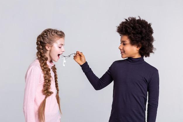 Met metalen vork. vastberaden jongen met wild haar die zijn vriendin voedt met een koptelefoon die verstrikt is in een metalen vork