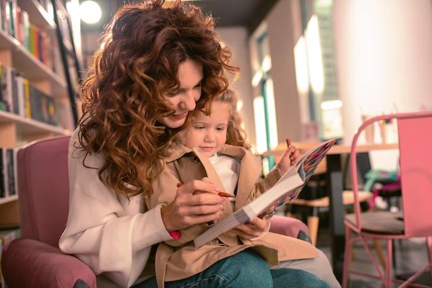 Met mijn hulp. mooie brunette vrouw boek kijken terwijl haar kind omhelzen