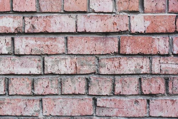 Met mortel bedekte rode bakstenen muur met zeer oude en gebarsten stenen