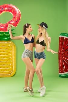 Met opblaasbare zwemcirkel. zomer portret kaukasische tieners op een groene achtergrond.