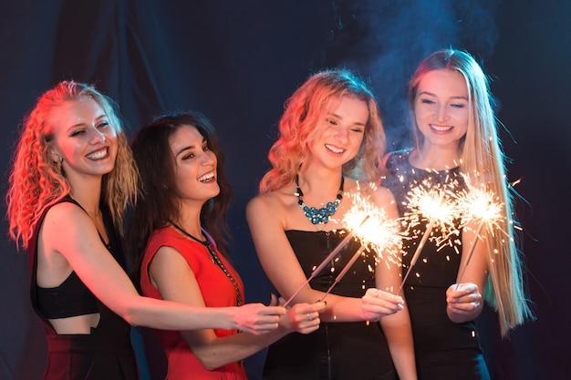 Met plezier vieren. groep vrolijke jonge vrouwen die sterretjes dragen. nieuwjaar, feestdagen en feestconcept.