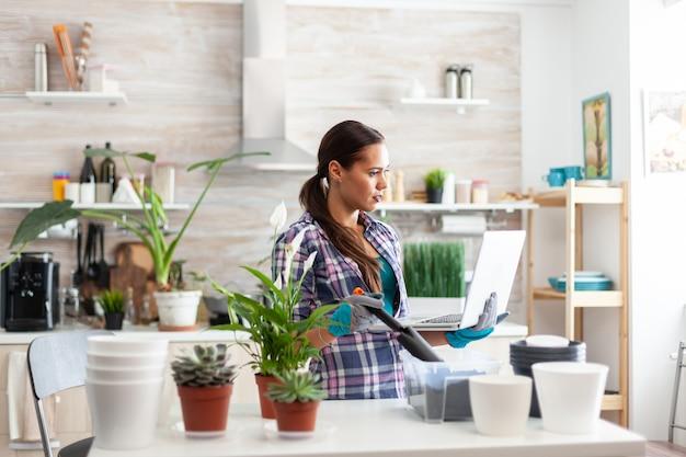 Met schop voor tuinieren en laptop in keuken op zoek naar woondecoratie