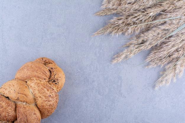Met sesam bedekt strucia-brood naast stengels van gedroogd verengras op een marmeren oppervlak