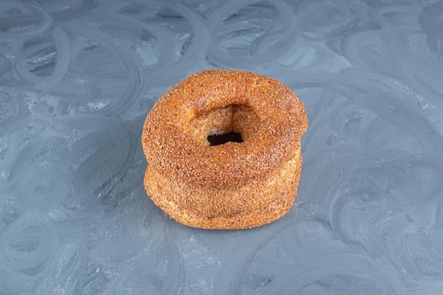 Met sesam bedekte bagels gestapeld op marmeren tafel.
