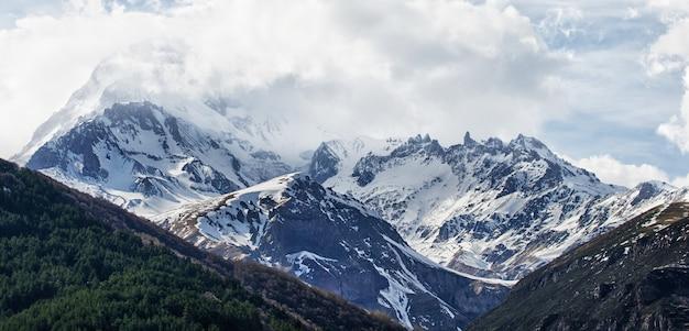 Met sneeuw bedekte bergen van de kaukasus, mount kazbek in de wolken