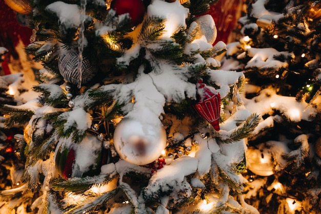 Met sneeuw bedekte kerstboomtakken versierd met gouden feestelijke ballen, speelgoed en lichtjes nieuwjaar