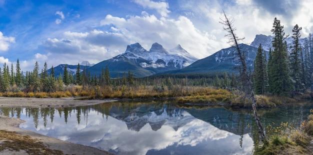 Met sneeuw bedekte the three sisters trio pieken berg met blauwe lucht en witte wolken reflecteren op het wateroppervlak